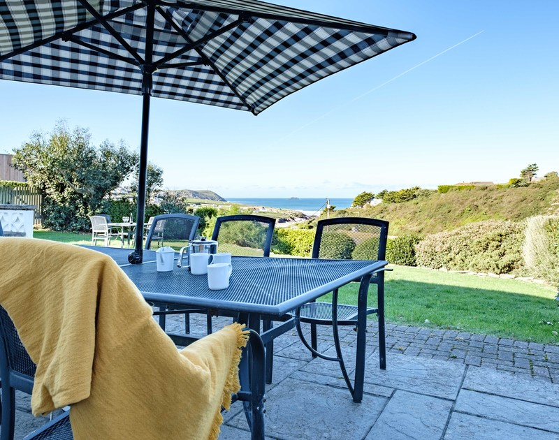The views reach down the garden and out over the sea towards Stepper Point from the sheltered patio area outside at self catering holiday house Westpoint in Polzeath.