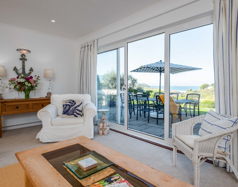 Sea views from the sitting room beyond the garden and outdoor patio area at Westpoint, a self catering holiday home to rent in Polzeath, North Cornwall.