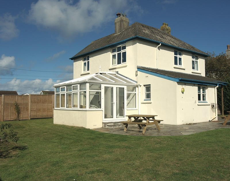 A view from the garden of the lawns, patio and conservatory at Trevian, a self catering holiday rental in Rock, Cornwall.