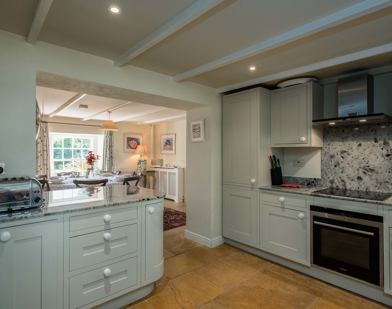 The open plan dining room/kitchen at Old Farm with polished granite worktops and limestone flooring.