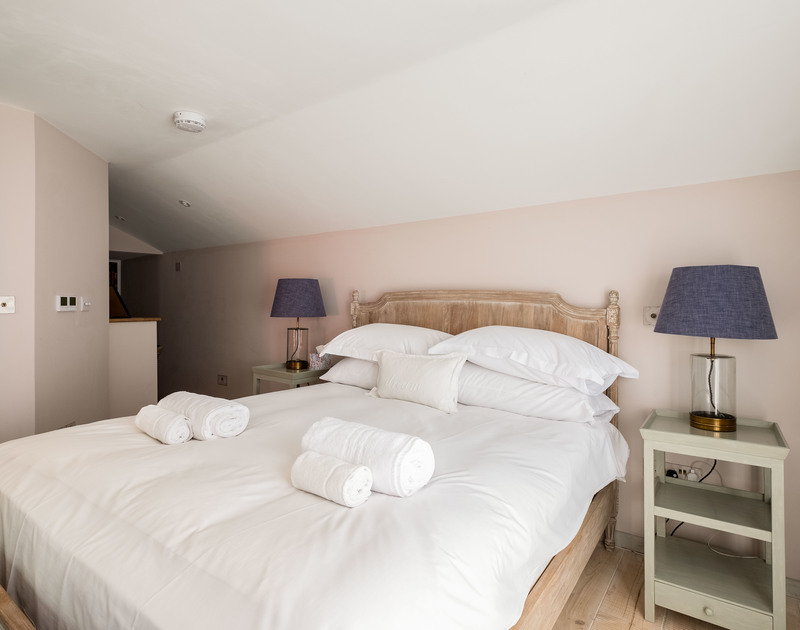 The additional king size bedroom with ensuite bathroom accessed via the lounge at Old Farm, a luxury holiday house in Daymer Bay, North Cornwall.