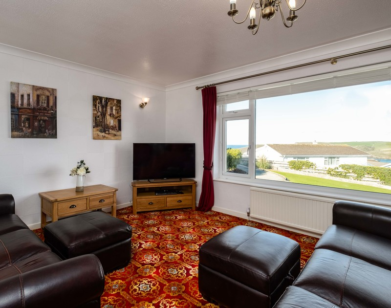 The traditional lounge with a large window at Hillview, a self catering seaside holiday rental with views overlooking Polzeath in North Cornwall.