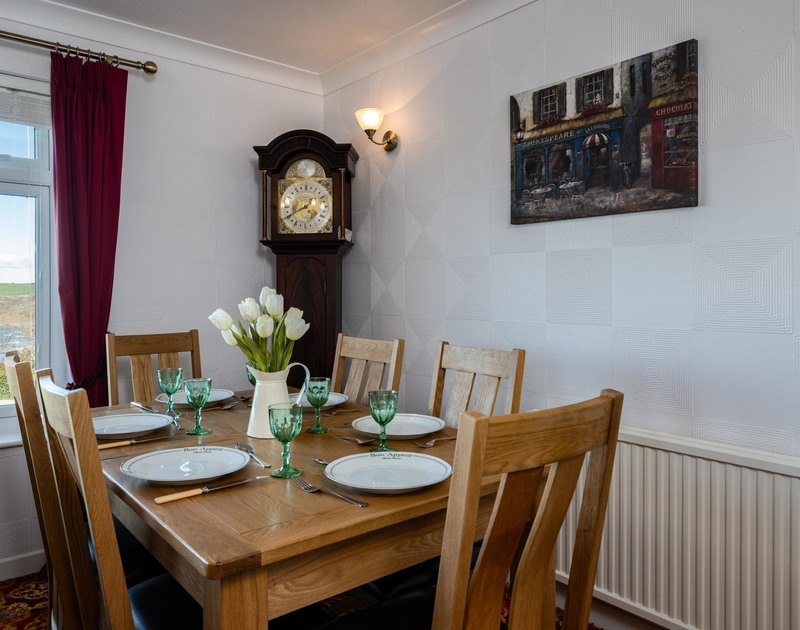 A traditional Grandfather Clock beside the dining table in the lounge at self catering holiday house Hillview in Polzeath.