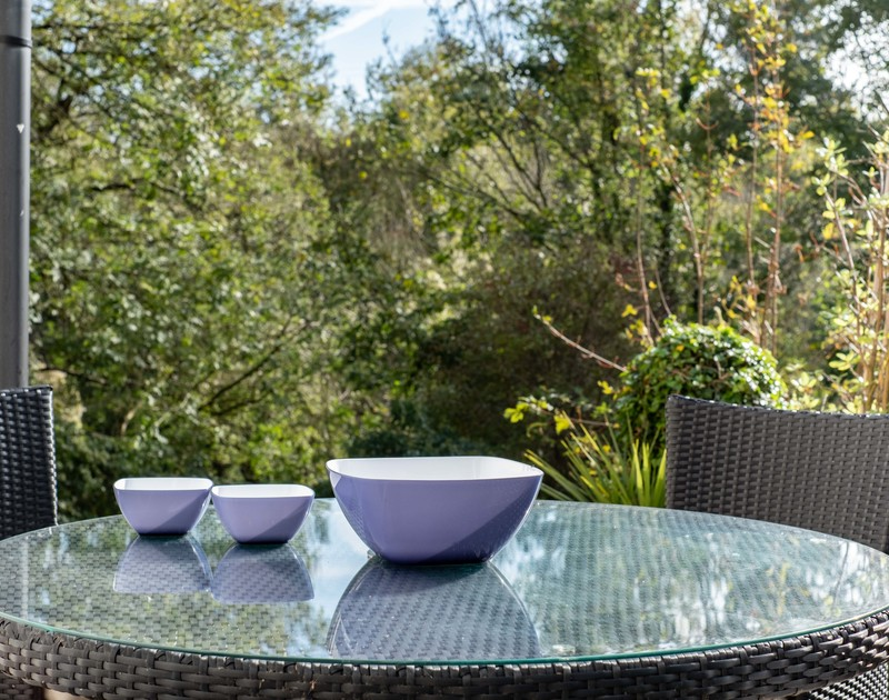 Glass topped outdoor table and chairs are perfect for alfresco food or drinks at self catering Alpine Lodge in Rock, north Cornwall.