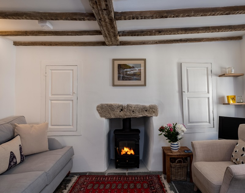 Exposed wooden beams and a granite lintel above the wood burner in the elegant sitting room at Mobray, self catering holiday accommodation yards from the harbour in Port Isaac in North Cornwall.