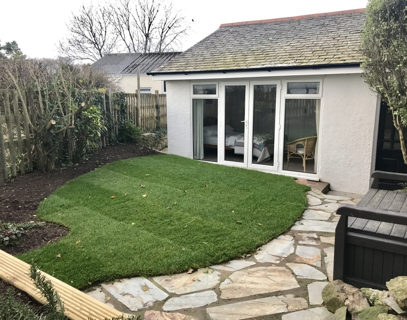 The small lawn and paved areas in the garden at pretty converted barn Little Pityme in Rock, North Cornwall.
