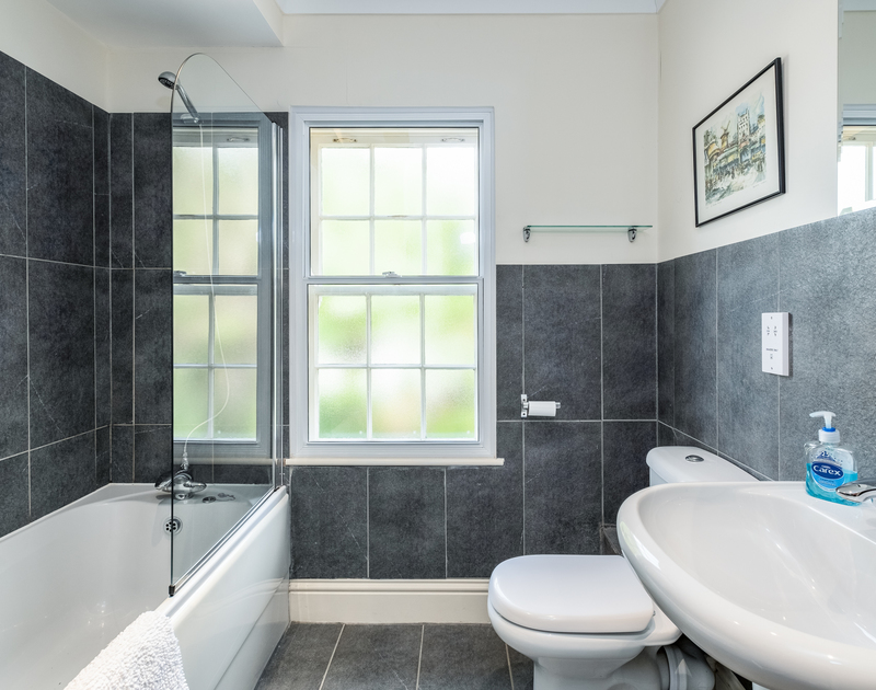 The bathroom with stylish grey tiles at Lowenna Manor a self catering, holiday rental in Rock, Cornwall.