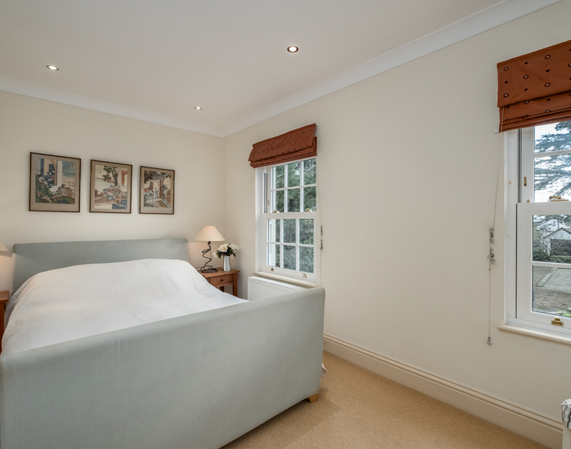 The master bedroom at Lowenna Manor 10 is light and bright with a kingsize bed and windows overlooking the communal gardens
