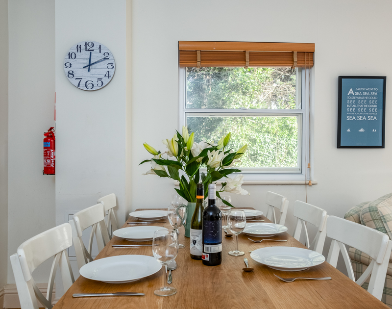 Enjoy a family holiday lunch in the dining room at Lowenna Manor 10, a holiday home to rent in Rock with views out to the garden