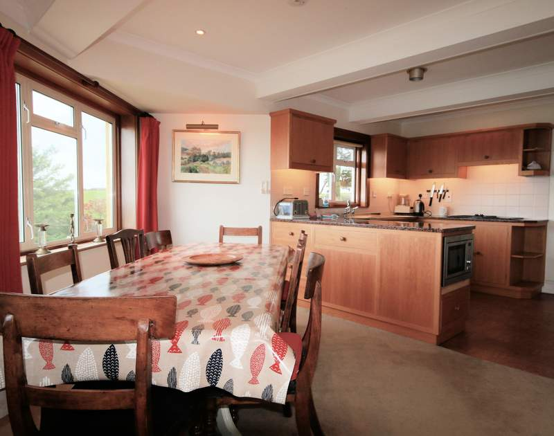 Room for all the family around the dining table in the window at Trevan House, a self catering holiday house in a glorious setting just beside the footpath down to beautiful Lundy Bay.