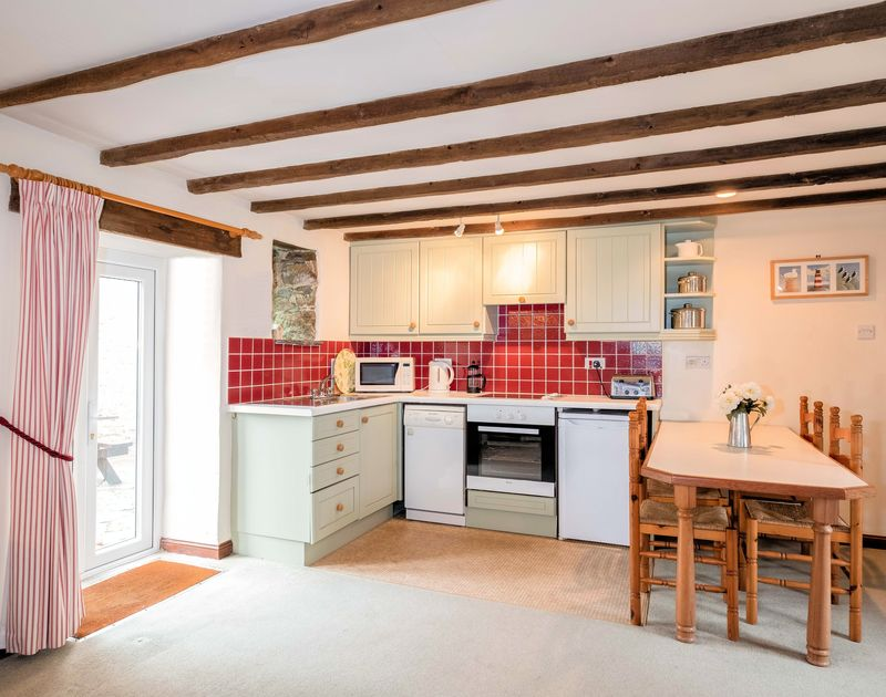 The pretty kitchen and dining table in The Granary, a self catering holiday house to rent in Rock, North Cornwall.