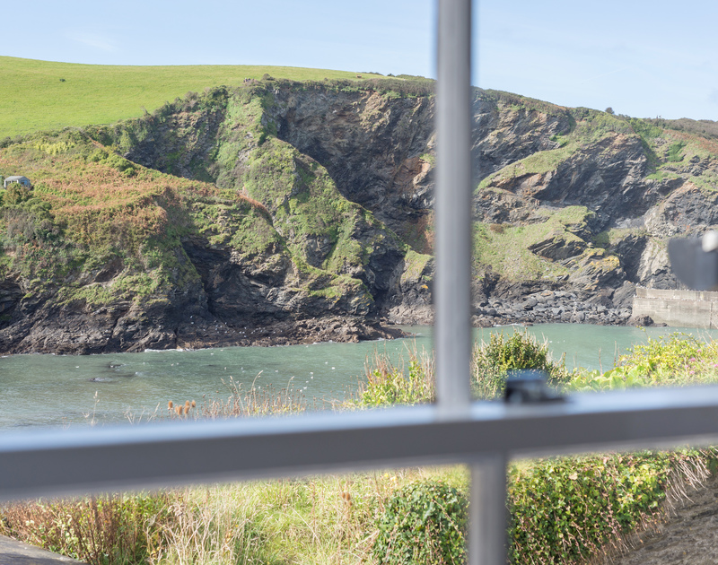 Views out across the harbour at Port Isaac to stunning Lobber Point through the pretty sash window of the bedroom at cosy romantic getaway Homestead.
