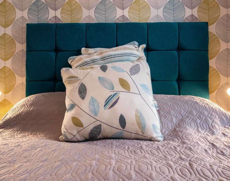 Rest and relaxation in the double bedroom with an upholstered headboard and a feature wall at The View, self catering holiday accommodation in Port Isaac in North Cornwall.