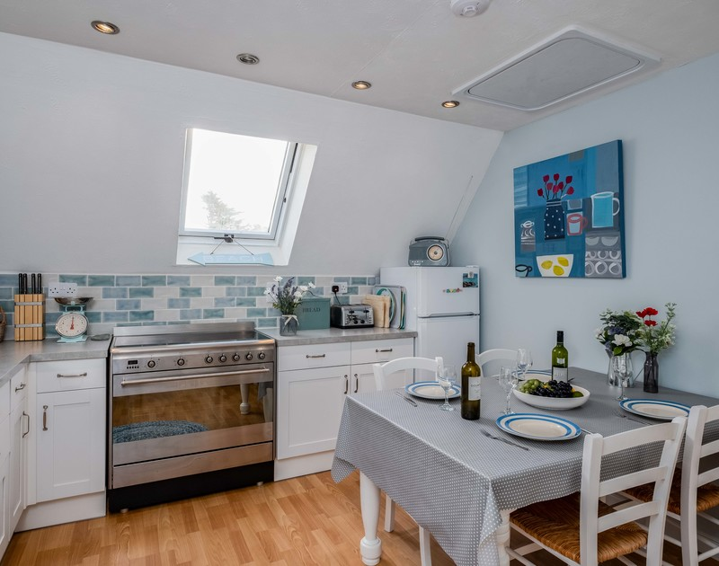 The well-equipped kitchen of Rocklings, a self-catering holiday house in Rock, Cornwall, with its breakfast table.