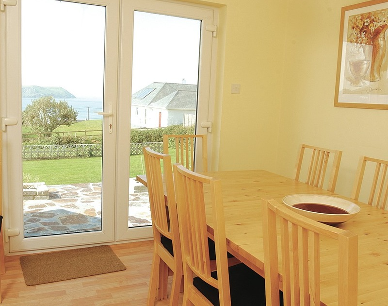The dining room with glass doors to patio at Chy-An-Var, holiday rental at Polzeath, with its lovely sea views.