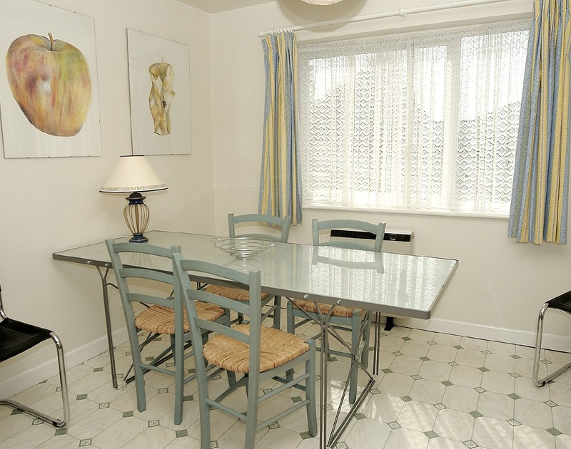 Dining area in holiday rental Caelum with glass topped dining table, window overlooking the front garden in Port Isaac, Cornwall.