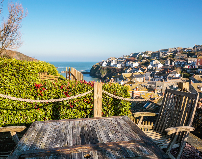 The stunning view of Port Isaac from the elevated outdoor seating area at Hillside Cottage self catering holiday home in Port Isaac.