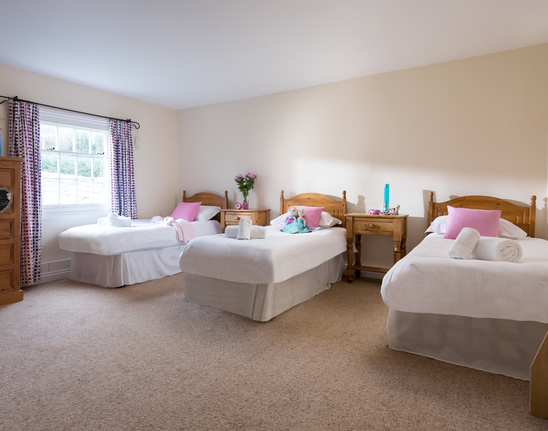 The triple bedroom with single beds at The Farmhouse holiday cottage in St Minver, Rock