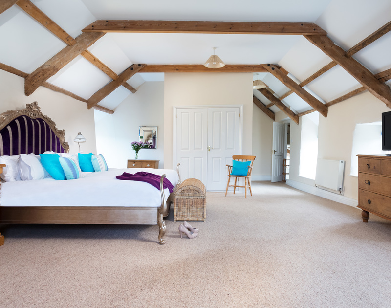 The master bedroom with emperor bed and large ensuite shower room at The Farmhouse holiday home in St Minver, Rock.
