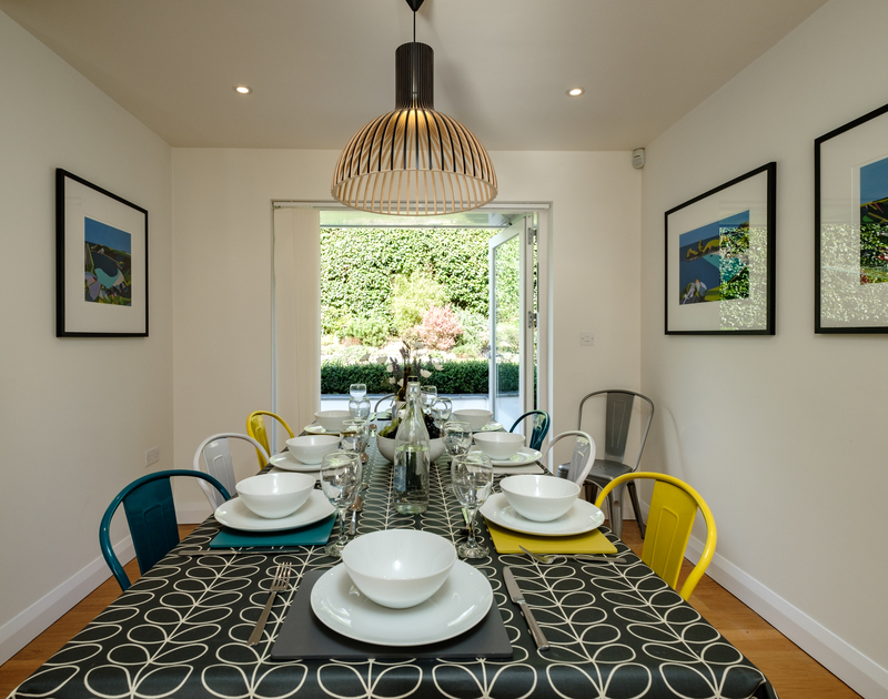 The dining room with patio doors to the garden at Out Of The Wind self catering holiday home in Rock, North Cornwall.
