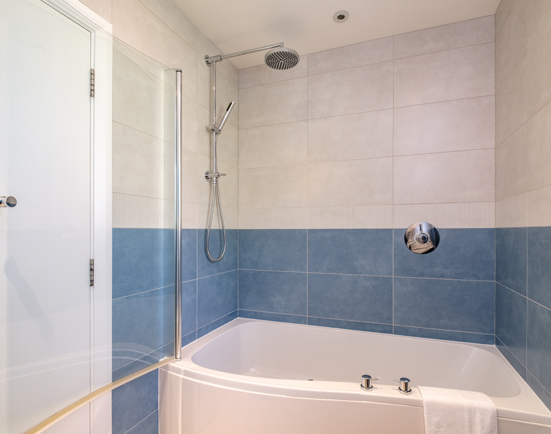 The ensuite bathroom with bath and shower at Out Of The Wind holiday home in Rock, North Cornwall.