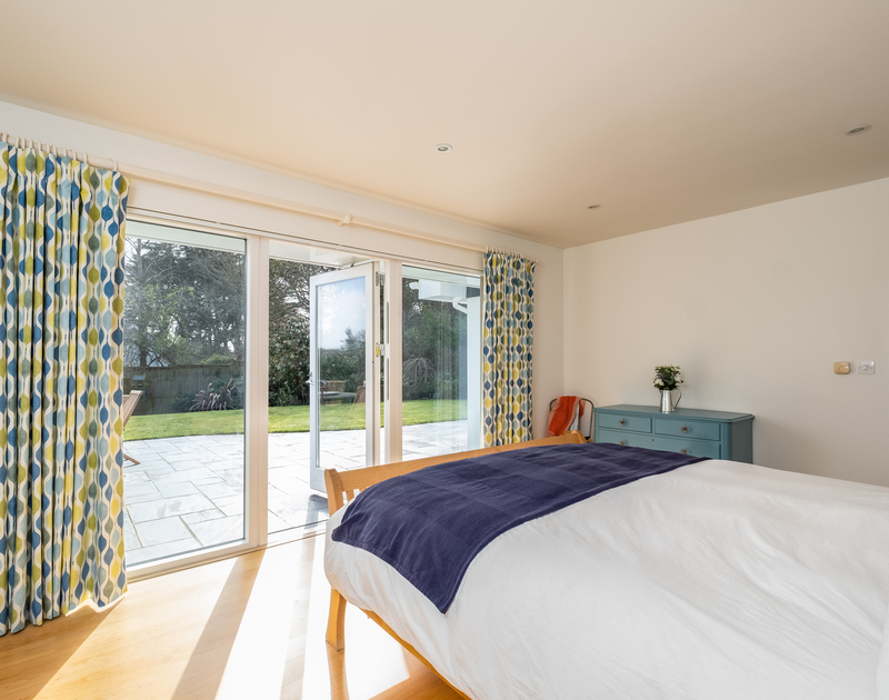 The master superking bedroom with large patio doors onto the garden at Out Of The Wind self catering holiday home in Rock, North Cornwall.
