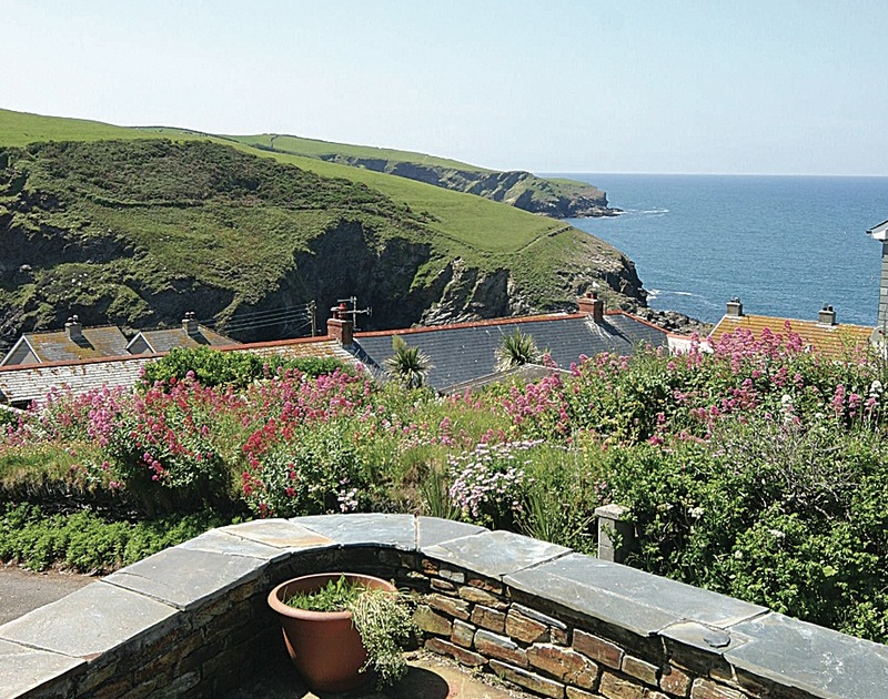 Views over the rooftops to the sea and coastline beyond from self catering Shilling Stones in Port Isaac, Cornwall.