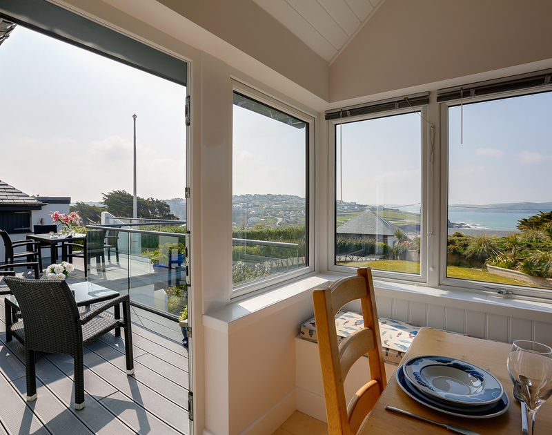The window seat and the dining table with large glass doors and windows with views over Polzeath and the rugged North Cornish Coastline at Clouds Hill.