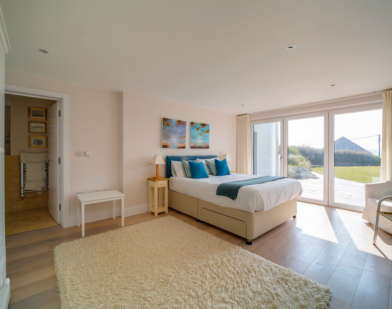 The second double bedroom with large glass doors out to the garden at luxury self catering holiday house Clouds Hill in New Polzeath.