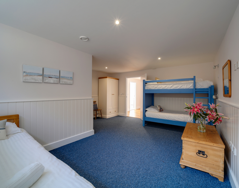 The triple bedroom with a single bed and a bunk bed and plenty of space at Clouds Hill, a luxury, self catering holiday property in New Polzeath.