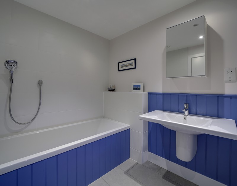 The bright family bathroom with a bath and overhead shower at Clouds Hill, a self catering, luxury holiday home in New Polzeath.