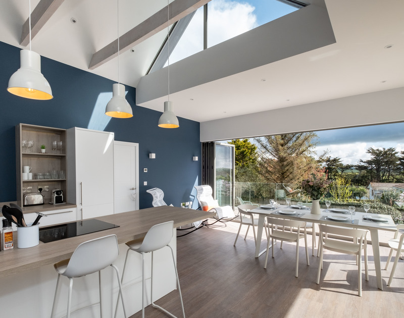 The modern and light open plan kitchen and dining area at Lowena self catering pet friendly holiday home in Polzeath, North Cornwall.