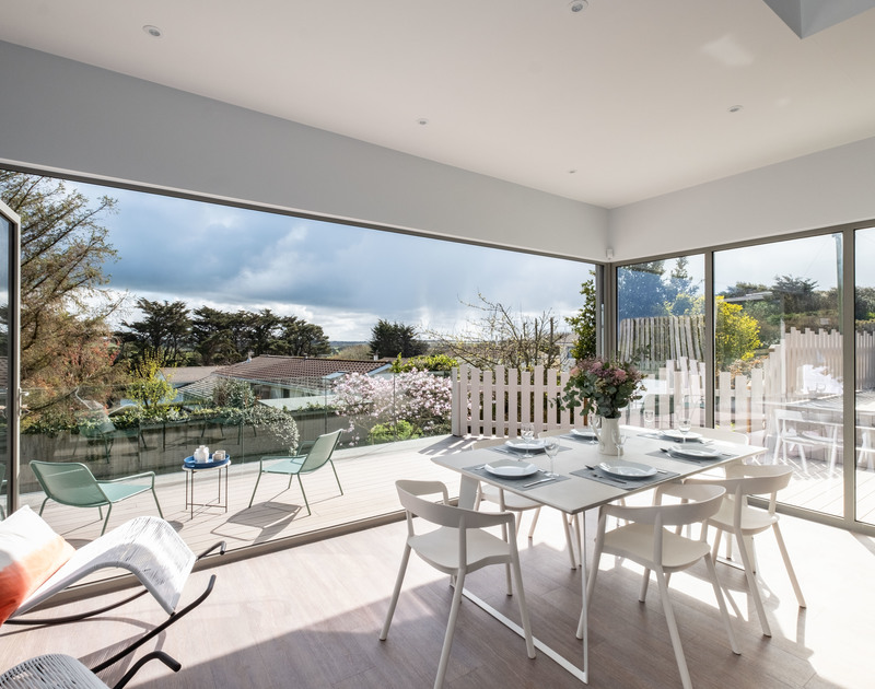 The dining room with floor to ceiling windows and patio doors opening onto the balcony at Lowena self catering holiday home in Polzeath, North Cornwall.
