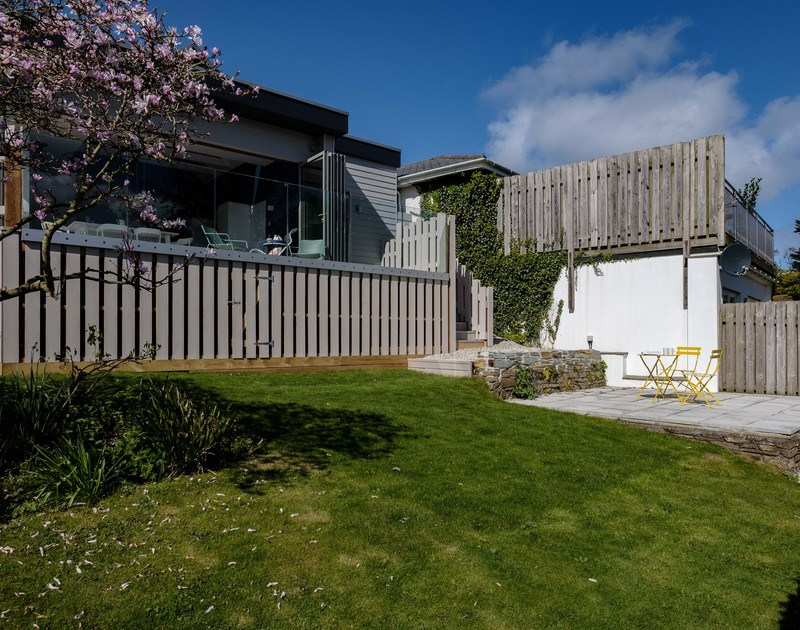 The sunny garden with outdoor seating area at Lowena self catering holiday home in Polzeath, North Cornwall.