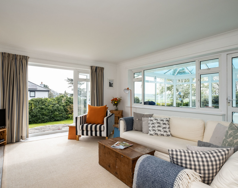 The living area with comfortable sofas and access out into the garden at Corriana, a self catering holiday house in the heart of Rock in North Cornwall.
