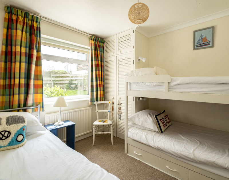 the contemporary triple bedroom at Atlantis with a bunk bed and a separate single bed, a self catering holiday house to rent in Polzeath, North Cornwall.
