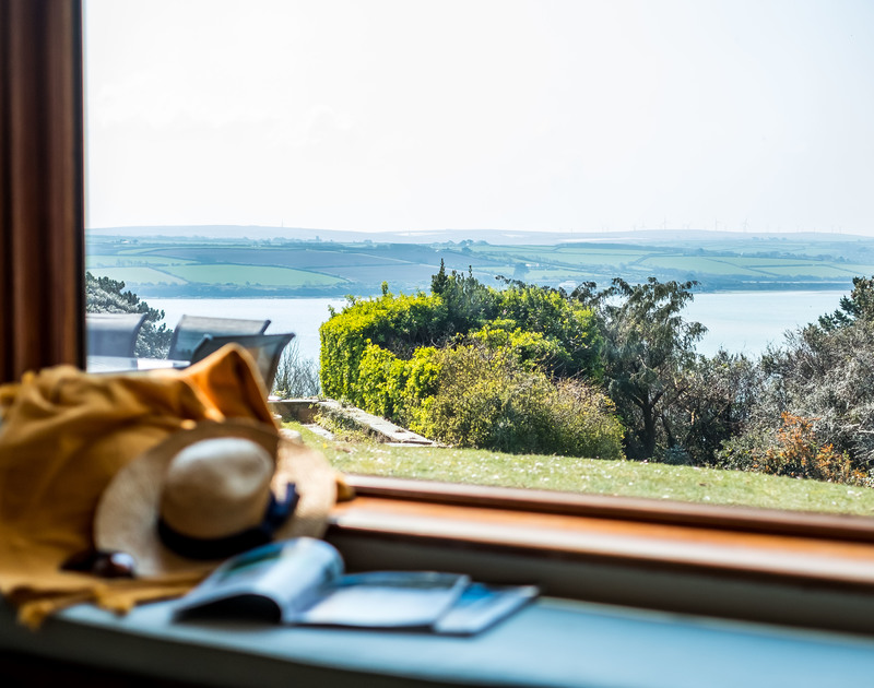 Large windows and a window seat make the most of the beautiful views over the Camel Estuary in Rock from the sitting room at self catering holiday rental Little Trig.