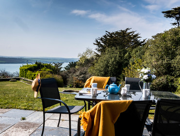 Enjoy a Cornish Cream Tea on the south facing terrace at self catering holiday rental Little Trig with extensive views down the garden and out over the stunning Camel Estuary in Rock, Cornwall.