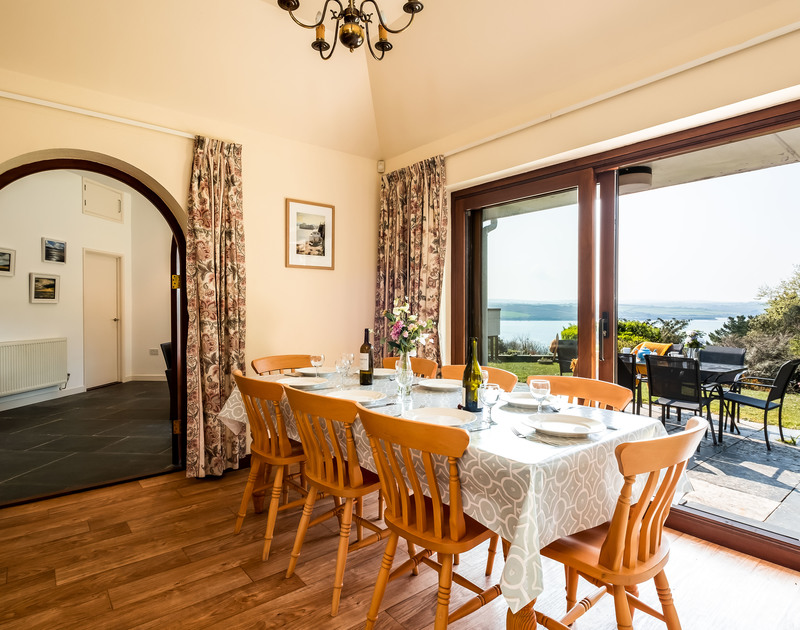 The dining room at self catering holiday rental Little Trig has a dining table with stunning Camel Estuary views from its elevated position above Rock in North Cornwall.