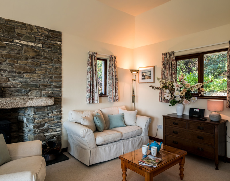 Exposed stone wall with a huge granite lintel over the feature fireplace in the sitting room at self catering holiday cottage Little Trig overlooking the Camel Estuary in Rock, North Cornwall.
