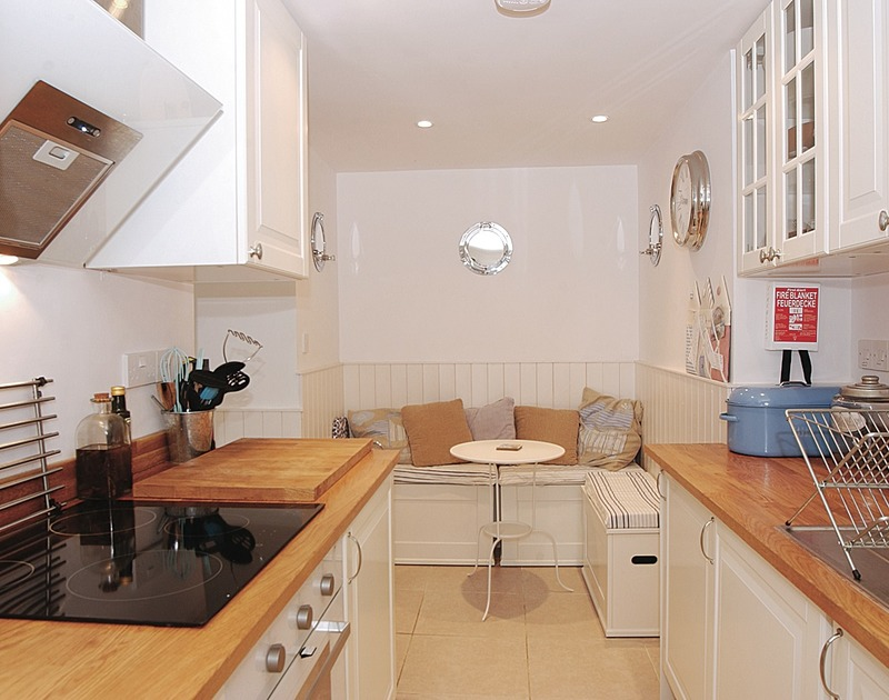 Galley style kitchen with cosy seating area in Bosun's locker, a romantic, self catering holiday retreat in Port Isaac, Cornwall.