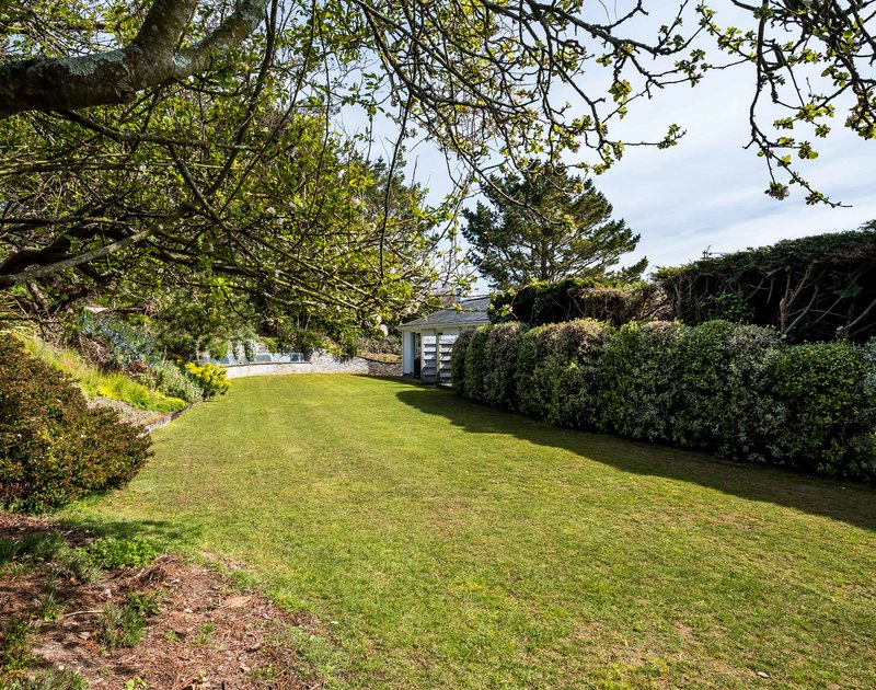 The well-maintained lawn and mature borders at Landers, a holiday house in Rock, Cornwall