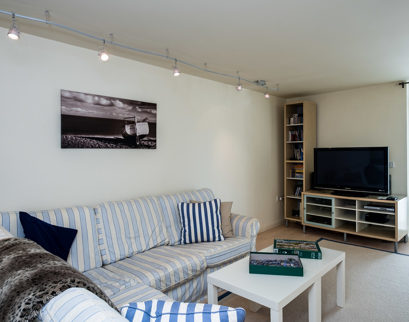 The comfy TV room at Landers, a holiday house to rent in Rock, Cornwall, with large TV and corner sofa.