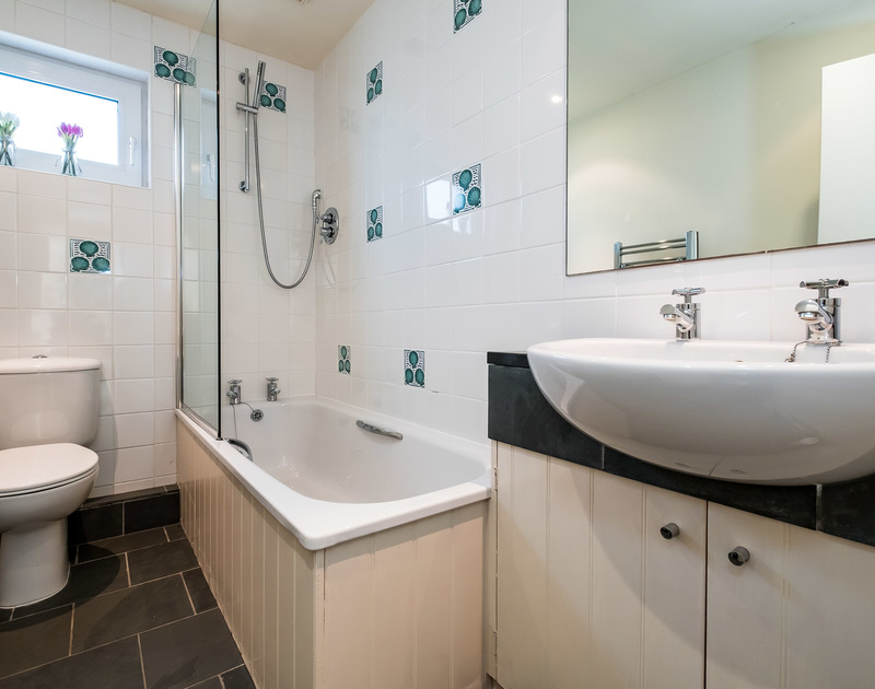 the family bathroom on the first floor in Landers; a bath with over head shower, W.C and basin