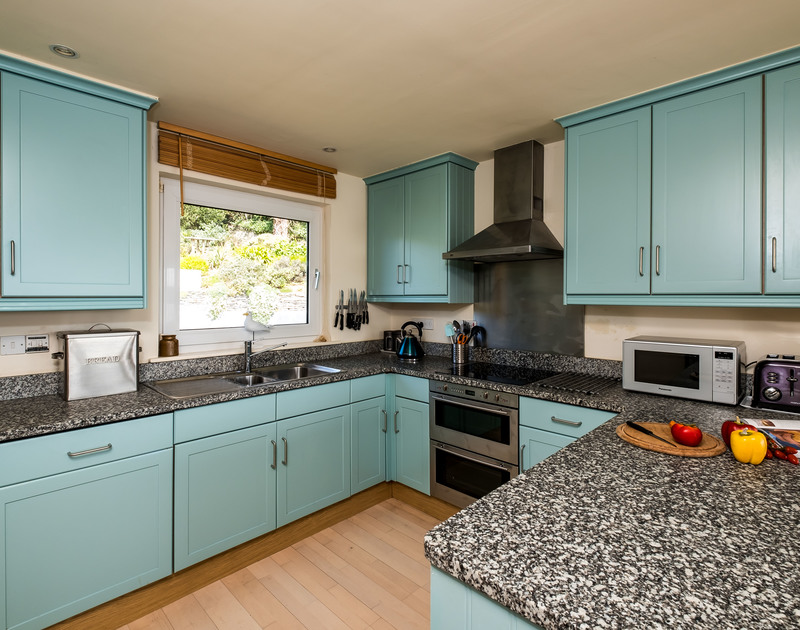 A contemporary style colourful kitchen at Landers, a holiday rental in Rock, Cornwall, with its breakfast bar.