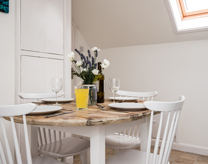 Enjoy a holiday meal at the light and bright dining table at Pinewood 14 self catering holiday home in Polzeath, North Cornwall.