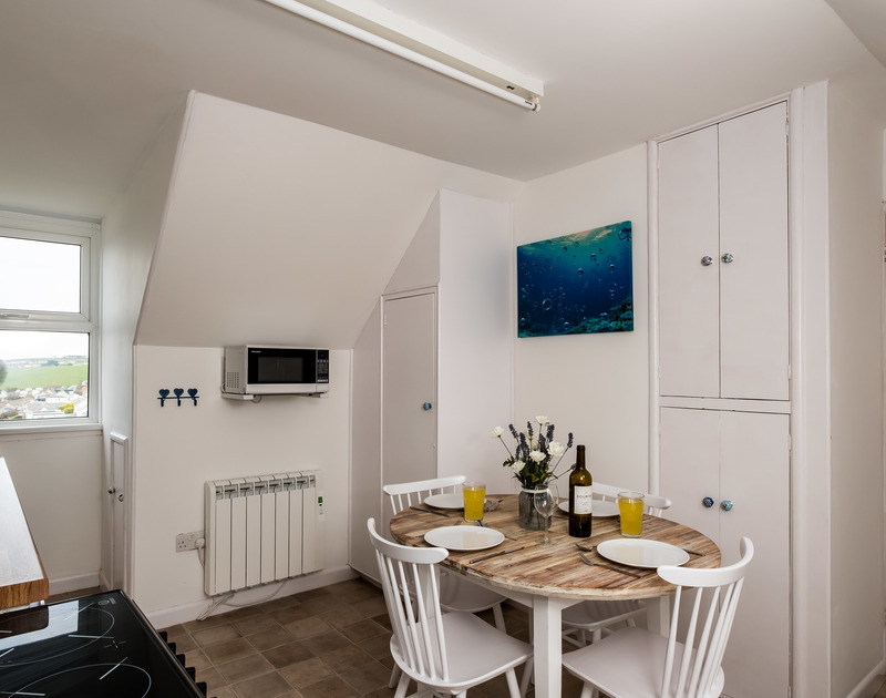 The light filled kitchen and dining area at Pinewood 14 self catering holiday home in Polzeath, North Cornwall.