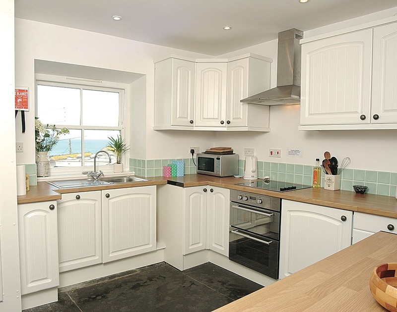 Well equipped kitchen with sea views at Stowaway, a self catering holiday apartment in Port Isaac, Cornwall.