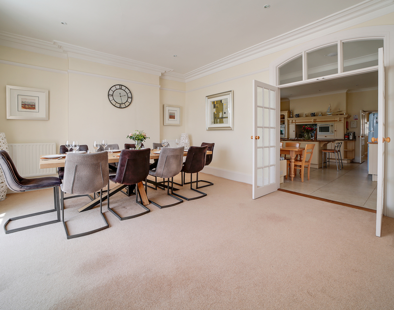 The spacious open plan living and dining area, with doors leading through to the kitchen at The Haven holiday home in Daymer Bay on the North Cornwall coast.