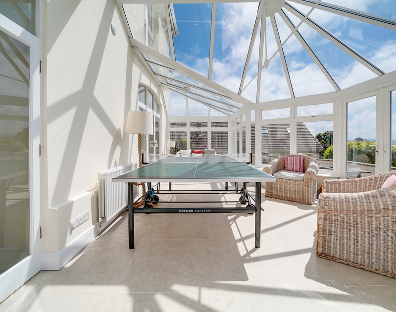 The large Conservatory leading to the garden with outdoor seating, tennis table and snug area at The Haven holiday home in Daymer Bay.